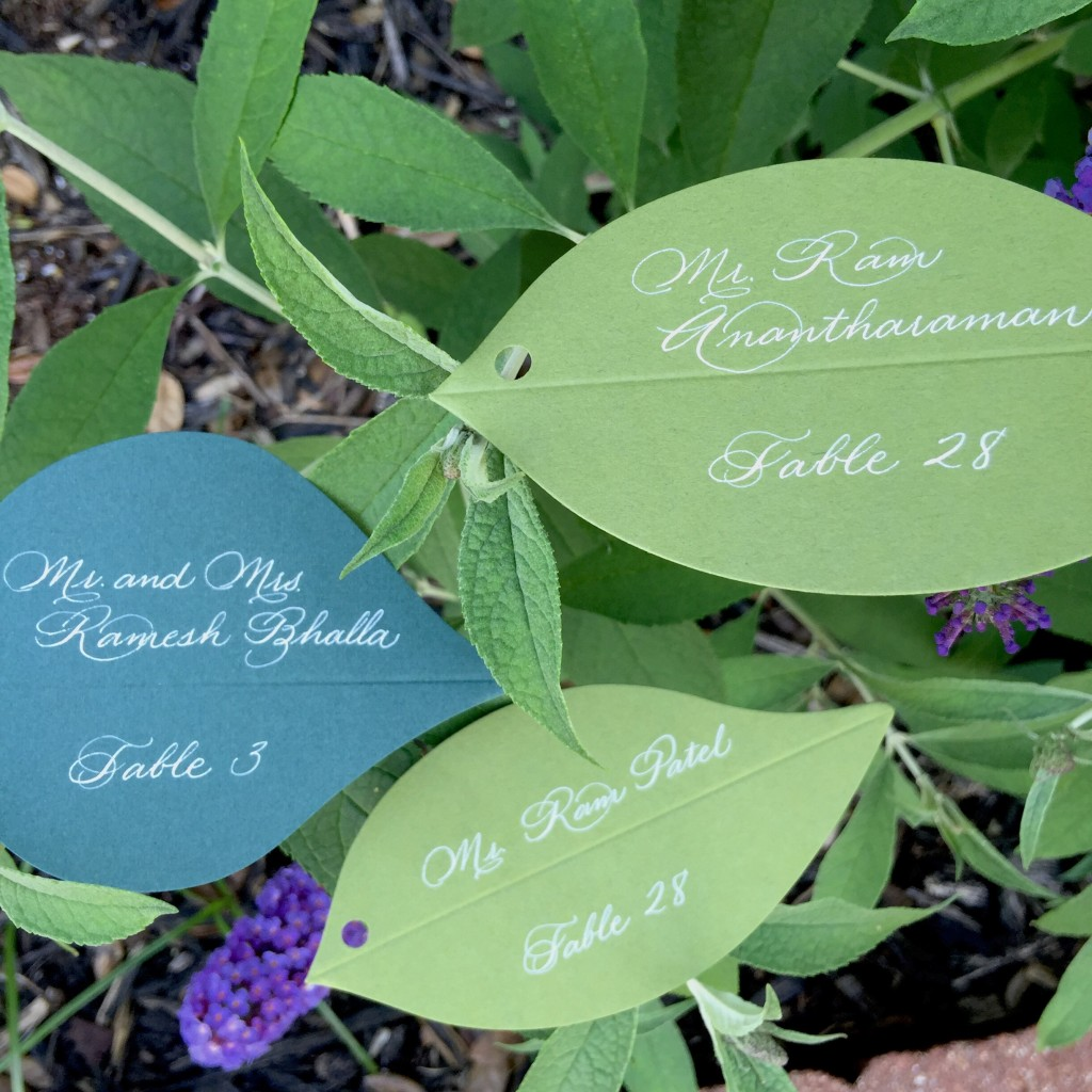 white and green escort card calligraphy on leaves